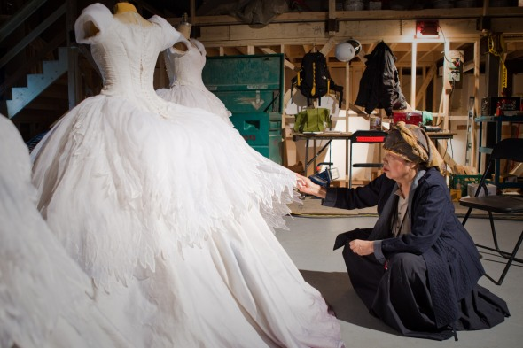 Costume Designer Eiko Ishioka examines Snow White's Swan Ball Gown, multiple copies were made due to the fact that Snow is exiled to the forest and trains with the Seven Dwarves in the same dress.